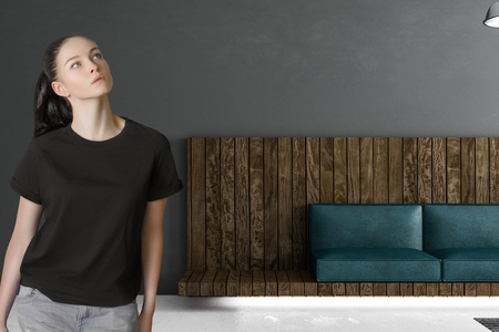 pondered woman in modern loft room with green leather coach in wooden framework