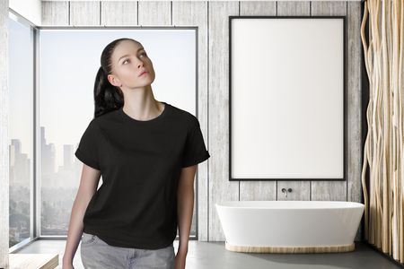 pondered woman in modern bathroom with mockup white poster on wooden wall