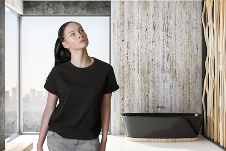 pondered woman in modern bathroom with black bath and city view from window floor-to-ceiling