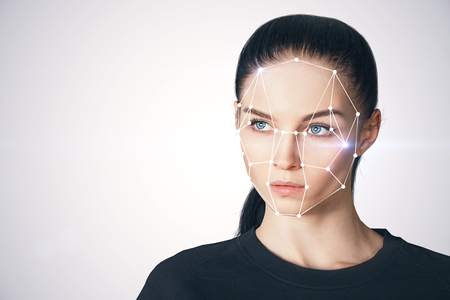 Portrait of attractive young european businesswoman with facial recognition system. ID and future concept