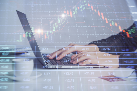 Hands typing on laptop. Business and Financial concept. Double exposure of stock market charts. 免版税图像