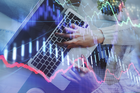 Hands typing on laptop. Business and Financial concept. Double exposure of stock market charts. Imagens