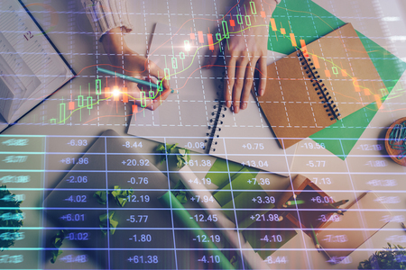 Close up of hands writing with double exposure of business charts. Financial concept. Imagens