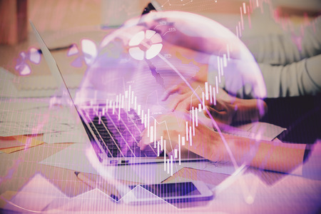 Hands typing on laptop. Business and Financial concept. Double exposure of stock market charts. Фото со стока