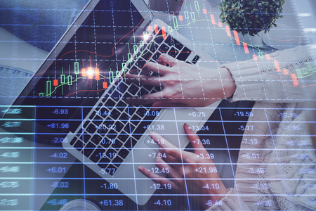 Hands typing on laptop. Business and Financial concept. Double exposure of stock market charts. Stok Fotoğraf