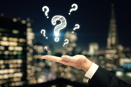 Doble exposición de manos de hombre con signos de interrogación. Concepto de pedir y buscar información.