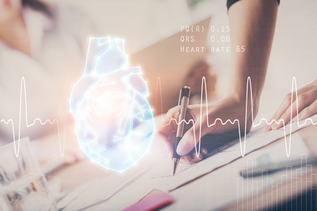 Heart hologram over womans hands writing background. Concept of Medical education study. Double exposure 写真素材