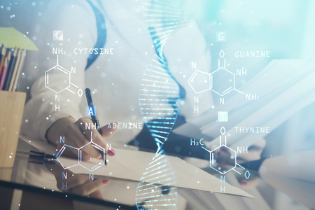 DNA theme hologram over womans hands writing background. Concept of education. Double exposure
