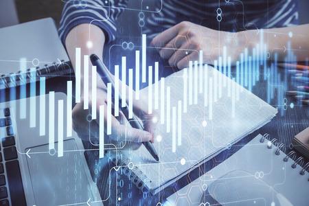 Financiële grafiek getekend over handen die aantekeningen maken Stockfoto
