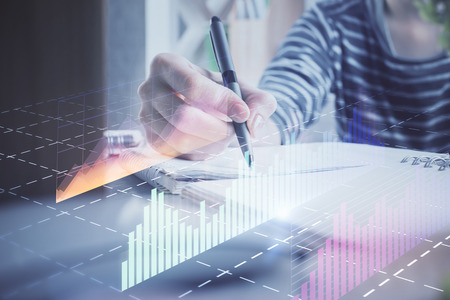 Financial forex graph drawn over hands taking notes