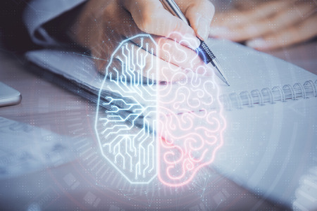 Double exposure of womans writing hand on  with brain hud. Concept of learning.