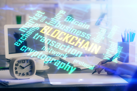 Cryptocurrency hologram over hands taking notes Stock Photo