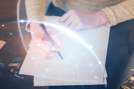 Social network theme hologram over hands taking notes Stock Photo
