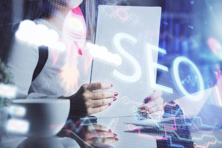 Double exposure of womans hands making notes with SEO icon. Concept of Search engine optimization Фото со стока
