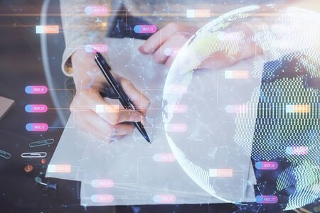 Multi exposure of hands making notes with world map hologram and data theme icons. Concept of global computer data.