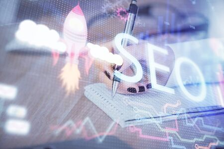 Double exposure of womans hands making notes with SEO icon. Concept of Search engine optimization Stock Photo