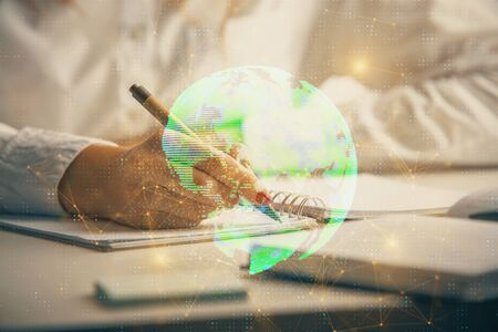 Social network theme hologram over hands taking notes background. Concept of global international people connect. Double exposure Stock Photo
