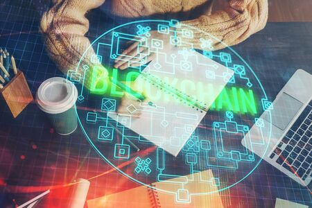 Cryptocurrency hologram over hands taking notes background. Concept of blockchain. Multi exposure Zdjęcie Seryjne - 124969348