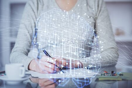 Double exposure of writing hand on background with brain hologram. Concept of learning. Imagens