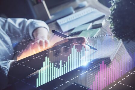 Financial forex charts displayed on womans hand taking notes background. Concept of research. Double exposure Banco de Imagens