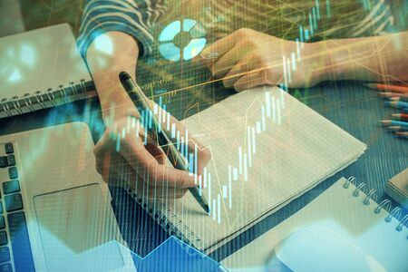 Financial chart drawn over hands taking notes background. Concept of research. Double exposure Stock fotó