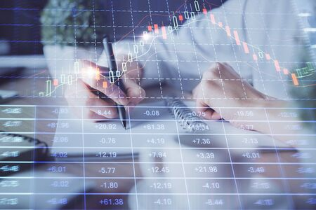 Financial forex graph displayed on hands taking notes background. Concept of research. Double exposure
