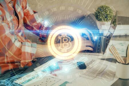 Crypto currency theme hologram with businessman working on computer on background. Concept of blockchain. Multi exposure. Imagens