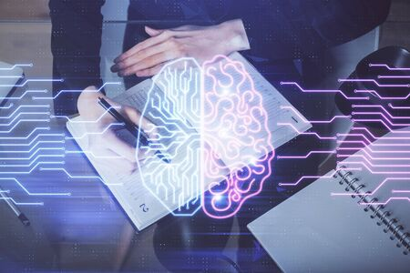Double exposure of writing hand on background with brain hologram. Concept of learning. Stock Photo