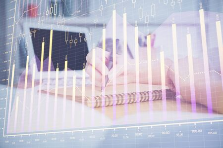 Financial graph displayed on womans hand taking notes background. Concept of research. Double exposure Stock Photo
