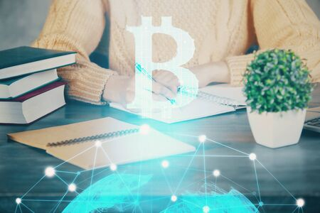Cryptocurrency hologram over hands taking notes background. Concept of blockchain. Multi exposure Stock Photo