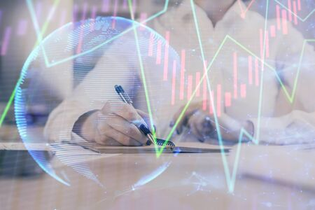 Financial chart drawn over hands taking notes background. Concept of research. Multi exposure Reklamní fotografie