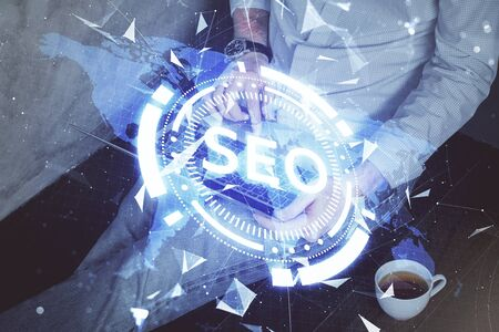Multi exposure of seo icon with man working on computer on background. Concept of search engine optimization.
