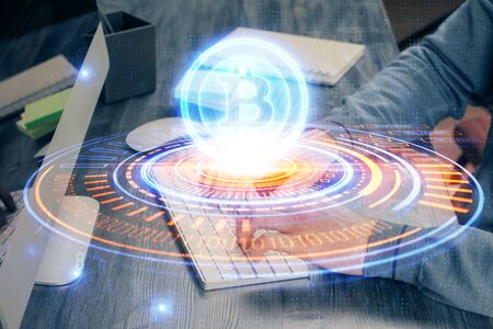 Crypto currency theme hologram with businessman working on computer on background. Concept of blockchain. Multi exposure. Reklamní fotografie