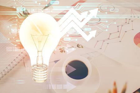 View of Bulb lamp idea concept icon on a futuristic interface with writing mans hand background. Double exposure.
