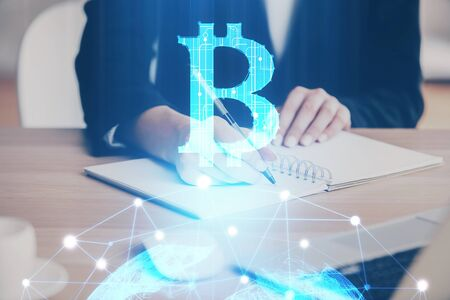 Cryptocurrency hologram over hands taking notes background. Concept of blockchain. Multi exposure Stok Fotoğraf