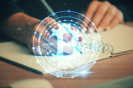 Cryptocurrency hologram over hands taking notes background. Concept of blockchain. Multi exposure Banco de Imagens