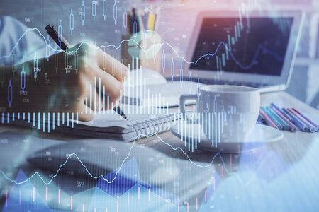 Financial chart drawn over hands taking notes background. Concept of research. Double exposure Stok Fotoğraf