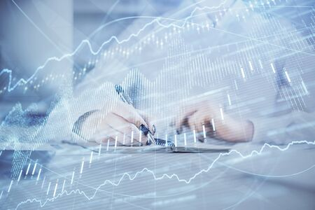 Financial chart drawn over hands taking notes background. Concept of research. Multi exposure Banco de Imagens