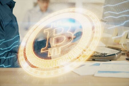 Crypto currency theme hologram with businessman working on computer on background. Concept of blockchain. Multi exposure. Banco de Imagens