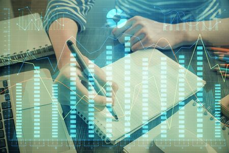 Financial chart drawn over hands taking notes background. Concept of research. Double exposure Stockfoto