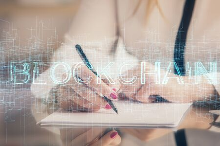 Cryptocurrency hologram over woman's hands writing background. Concept of blockchain. Double exposure 免版税图像