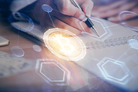 Cryptocurrency hologram over woman's hands writing background. Concept of blockchain. Multi exposure