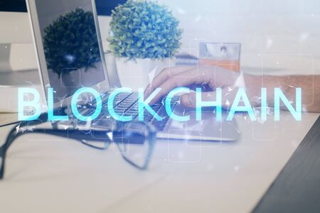 Crypto currency theme hologram with businessman working on computer on background. Concept of blockchain. Multi exposure. 免版税图像