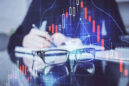 Forex chart hologram on hand taking notes background. Concept of analysis. Double exposure Standard-Bild