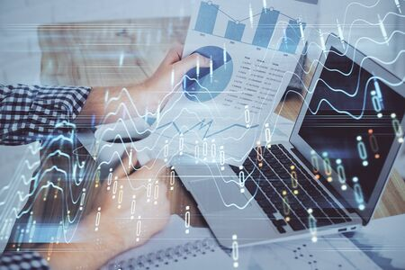 Forex graph with businessman working on computer in office on background. Concept of analysis. Double exposure. Archivio Fotografico