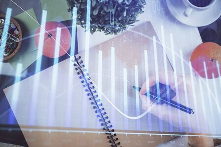 Forex chart hologram on hand taking notes background. Concept of analysis. Double exposure 写真素材