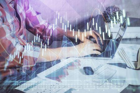 Doble exposición del gráfico de valores con el empresario escribiendo en la computadora en la oficina en segundo plano. Concepto de trabajo duro.