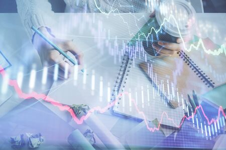 Financial forex graph displayed on hands taking notes background. Concept of research. Multi exposure