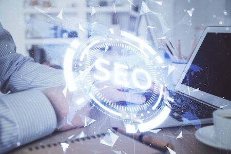 Double exposure of seo icon with man working on computer on background. Concept of search engine optimization. Stock Photo