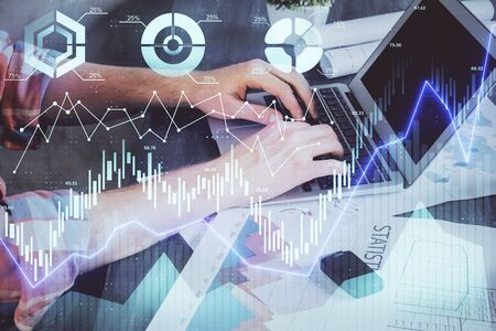 Double exposure of stock graph with businessman typing on computer in office on background. Concept of hard work.